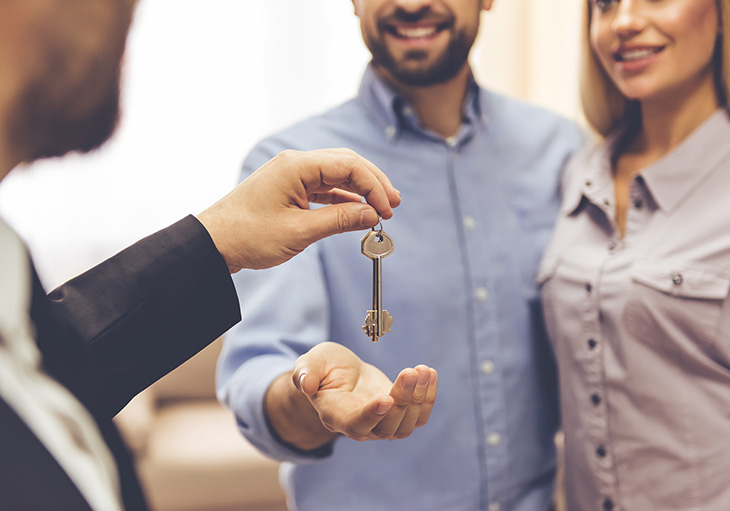 A man holds out his hand and accepts keys from a real estate agent to complete the last step in the home buying process.
