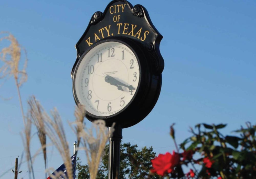 old-fashioned black street clock sign with the title city of katy texas painted at the top with a clear blue sky