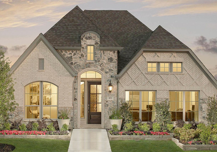 This Perry Homes' Design 2504W featuring light brick arranged in a herringbone pattern and a natural stone façade can help in