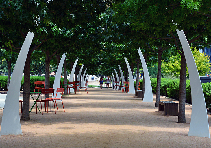 Tree-lined pathways and skyscrapers surround a large green area at Klyde Warren Park, just one of the best parks in Dallas, T