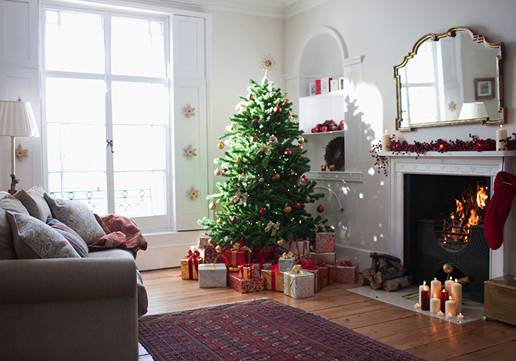 A decorated Christmas tree sits in the corner of a room, along with other holiday decorations.