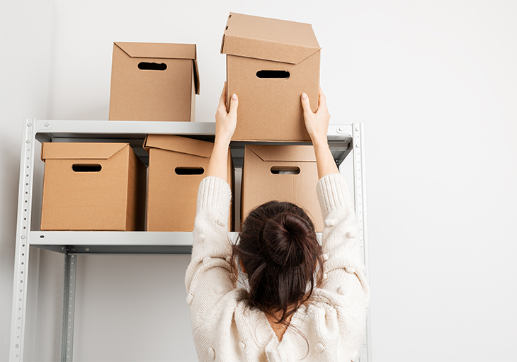 A woman retrieves a brown box from the top shelf of a