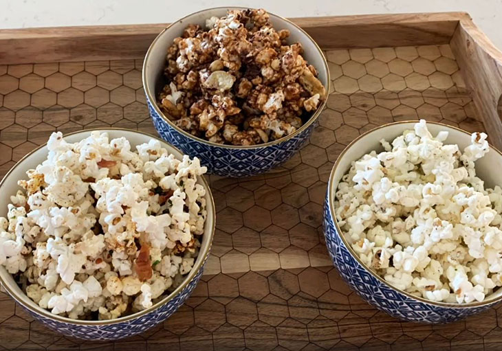 Close up photo of three blue ceramic bowls sitting on a wooden tray, that contain popcorn prepared with different seasonings.