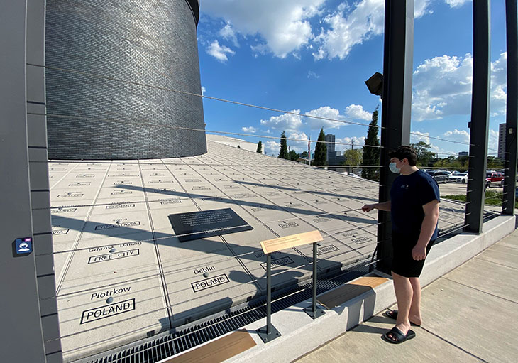 Young man stands looking at holocaust monument.