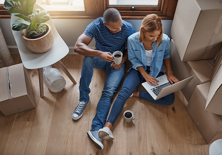 A man and woman sit on the floor and take a virtual home tour on their laptop.