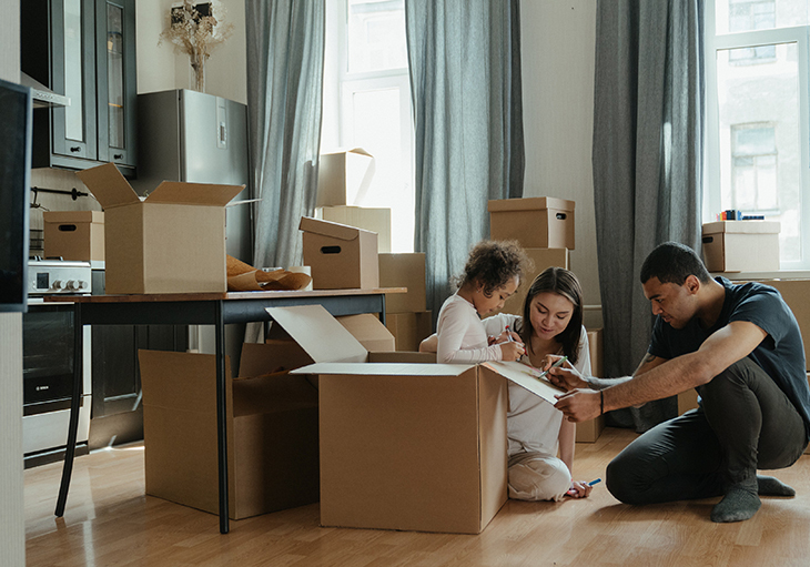 A family unpacks boxes in the kitchen of their new home.
