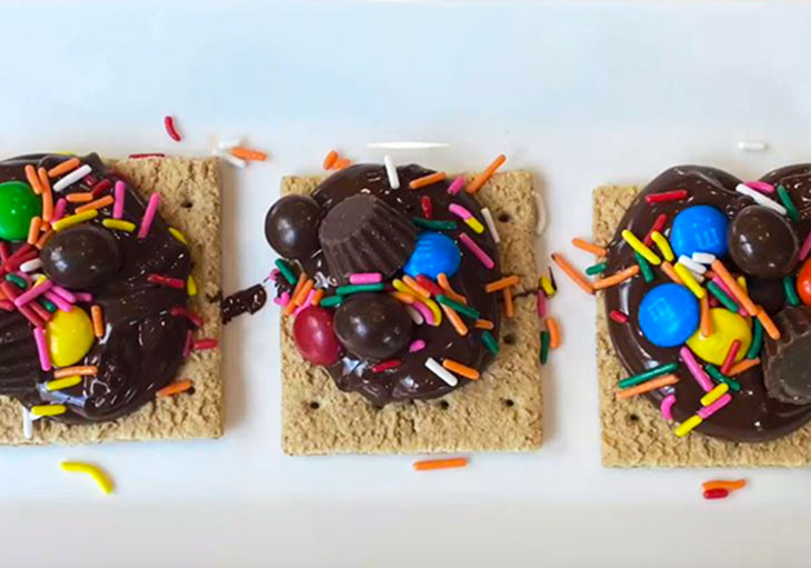 White square dishes contain graham crackers topped with chocolate, sprinkles, marshmallows and other candies.
