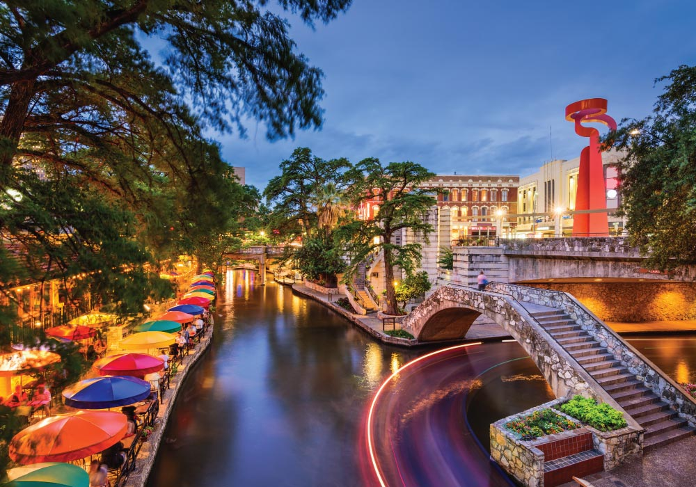 view from street level of san antonio riverwalk at dusk with colorful dining table umbrellsas and partly cloudy sky