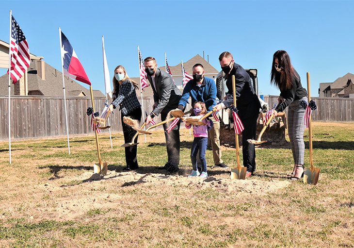 Perry Homes representatives, Stephen Netzley and daughter lifting shovels with scoops of dirt on the new homesite.