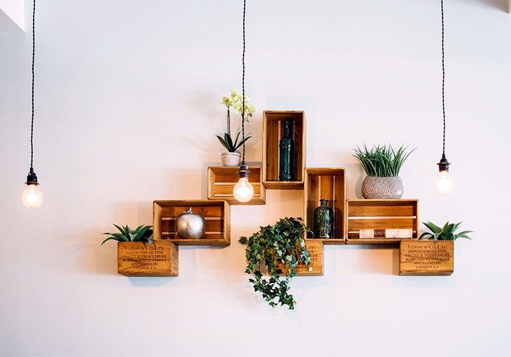 Eight small wooden crates decorated in various plants, vases and bowls hang on a wall behind three simple, single-bulb light