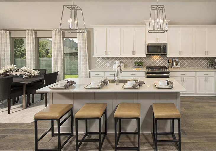 A beautifully designed kitchen features a large island and four brown leather bar stools.