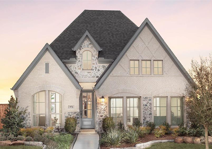 This Perry Homes' Design 1950W features light natural brick arranged in a herringbone pattern and a natural stone façade