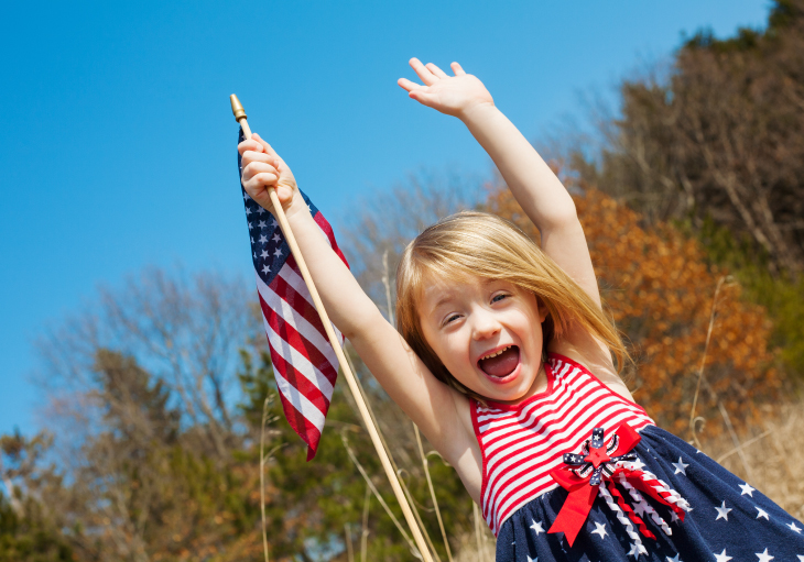 young girl in a field wearing stars and stripes sun dress with hands in the air holding a small american flag