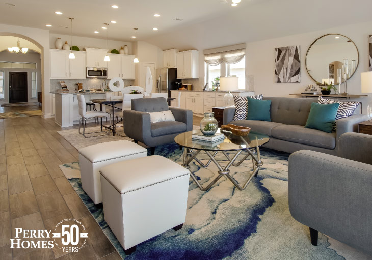 blue and white area rug in a living room with grey couches and white accents