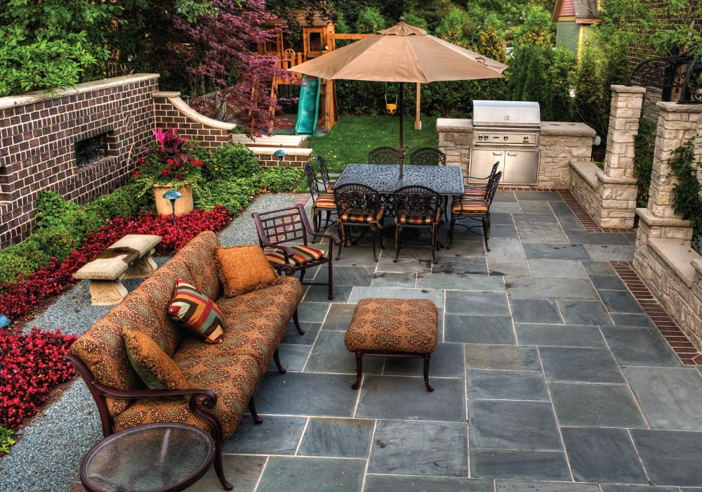 slate tile backyard patio with rod iron furnitiure, built-in grill, lush landscaping and children's play structure