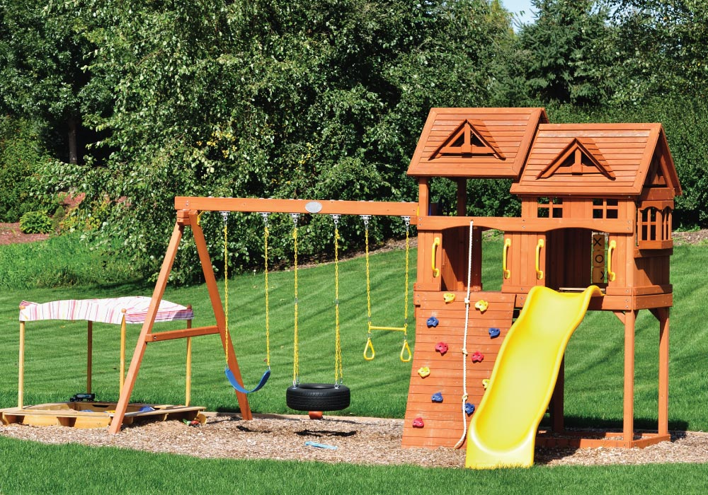 children's outdoor wooden play structure with slide, climbing wall, tire swing, rope climb, trapeze swing, fort and sandbox