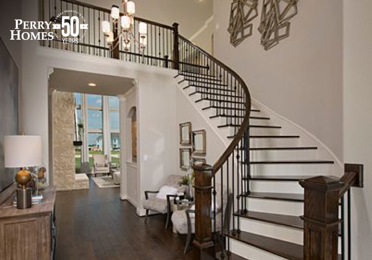 entry foyer of two story home with curved staircase with dark stained wood banister and treads and rod iron spindles