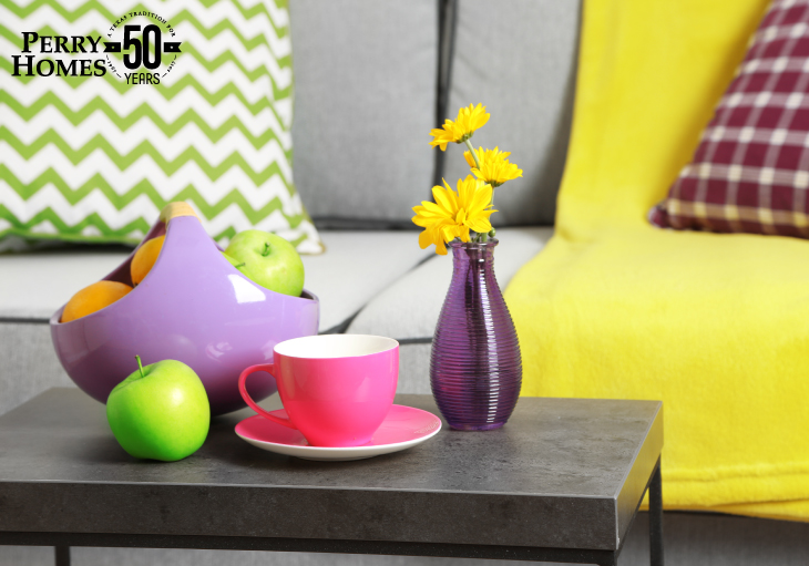 Gray table with flowers and brightly colored plate and cups