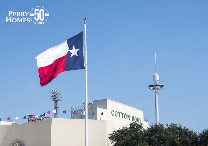 texas state flag blowing in the wind with the cotton bowl stadium and needle in background