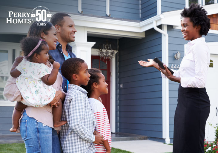 real estate agent showing a family of five the exterior of a two story blue sided home with red front door