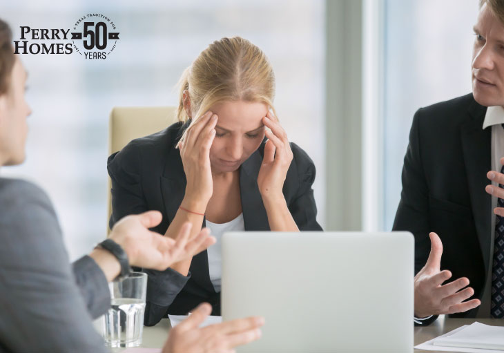 three people wearing suits in meeting seated at conference table as woman rubs her head in frustration