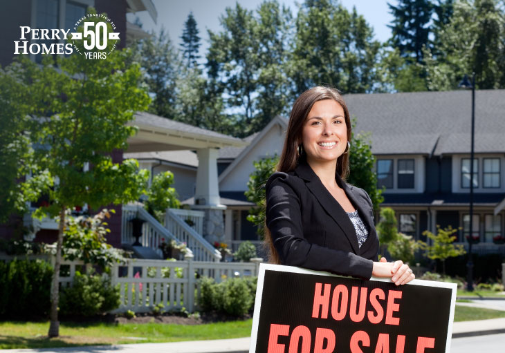 female real estate agent in a suit standing in front of a house leaning on a house for sale sign