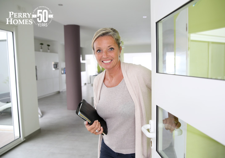 smiling woman faces reader as she opens modern glass door into white contemporary living space with mauve center column
