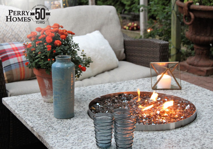 outdoor fire pit with stones within a marble topped table next to an outdoor wicker sofa