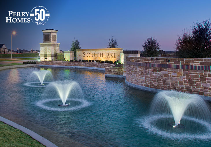 southlake community monument with pond and three fountains illuminated at night