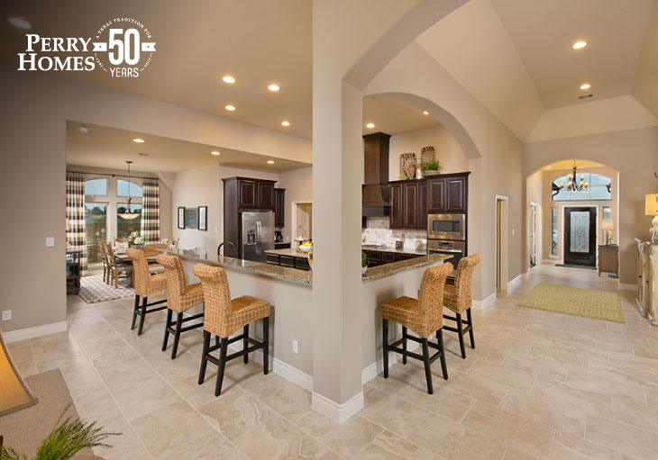 open-concept kitchen with dark brown cabinets, wrap around counter seating, dining area and vaulted foyer