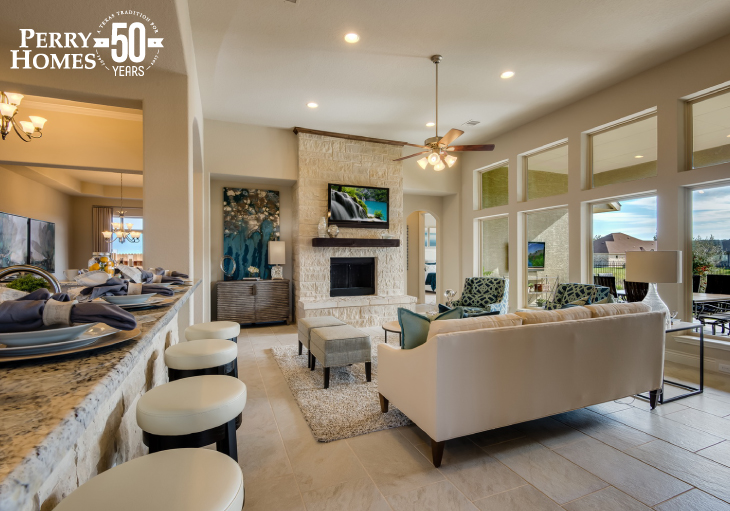 open concept family room with large picture windows light beige stone fireplace and wrap around kitchen counter seating