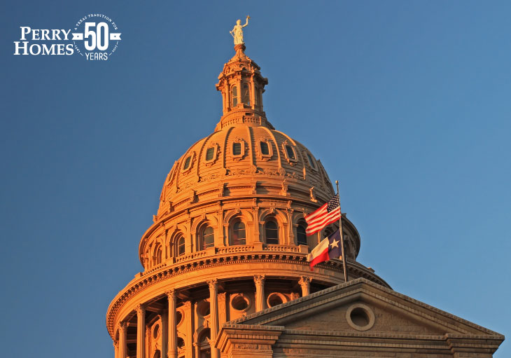 exterior of texas state capitol building rotunda at dusk with blue sky and american and texs flags blowing in the wind