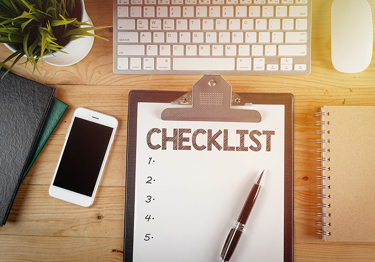 A blank checklist for your move-in ready home planning on a black clipboard sits atop a wooden desk next to a white smartphone, keyboard, computer mouse, notebooks and a potted plant.