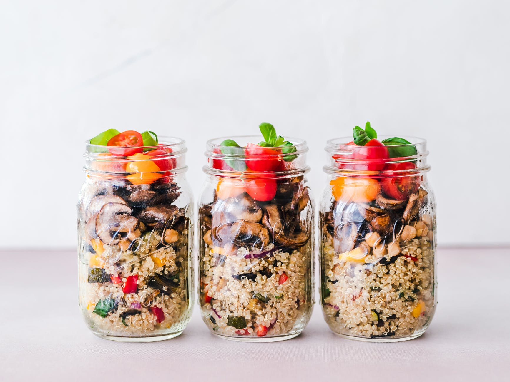 Three mason jars filled with a mixture of quinoa and colorful vegetables show how healthy and easy make-ahead lunches can be.