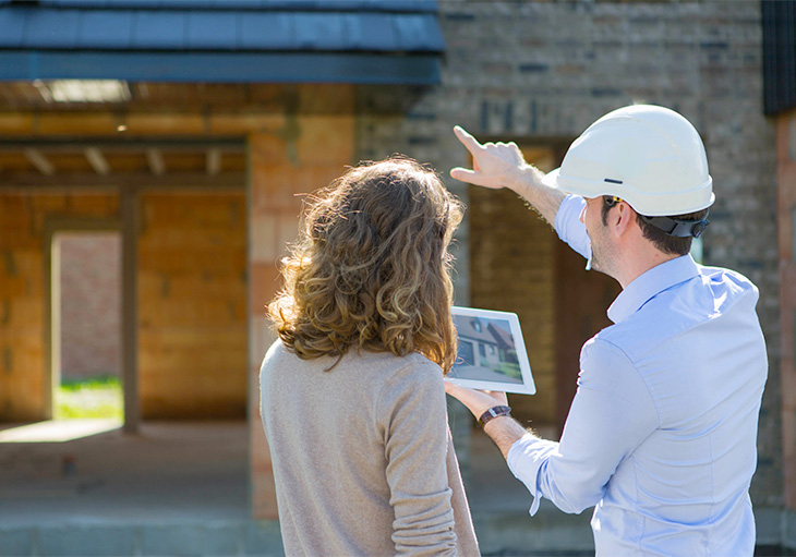 A home inspector wearing a white hard hat shows a photo of a house on a table to a woman while pointing at the brick and wooden structure in front of them.