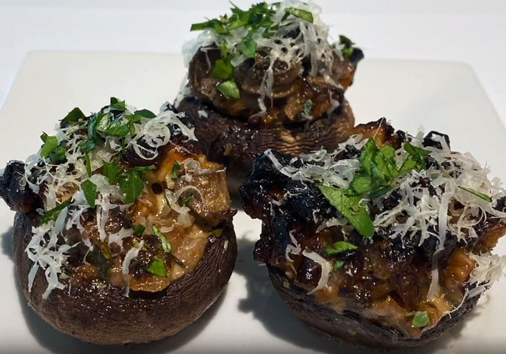 Close up of cooked mushrooms stuffed with garlic and walnut are displayed on a white dish with garnish.